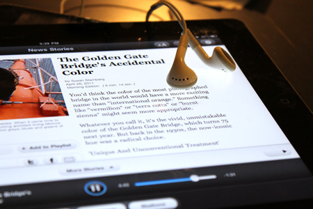 Earbuds draped over iPad with NPR app on-screen