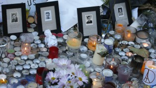 Pictures of victims are placed behind candles  outside the Bataclan concert hall in Paris, Sunday, Nov. 15, 2015. Thousands of French troops deployed around Paris on Sunday and tourist sites stood shuttered in one of the most visited cities on Earth while investigators questioned the relatives of a suspected suicide bomber involved in the country's deadliest violence since World War II.(AP Photo/Christoph Ena)