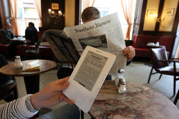 Man reading a newspaper next to man reading news on a Kindle