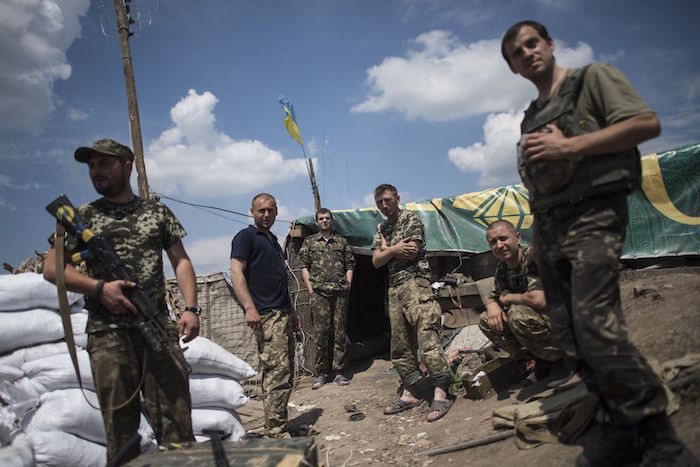 Ukrainian soldiers stand at their position near the division line with separatists in Marinka, near Donetsk, eastern Ukraine, Friday, June 5, 2015. As fears persist that eastern Ukraine is about to fall back into full-scale war, a leader of the international monitoring group is urgently calling for resumed negotiations. (AP Photo/Evgeniy Maloletka)